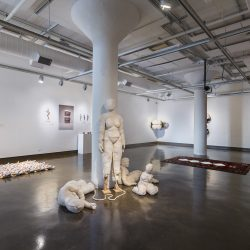 "An installation view of the exhibition titled, ""Once Upon A Time"" at the SVA Chelsea Gallery. A sculpture by Ella Hilsenrath is featured in the center of the photograph with other artworks hanging on the walls in the background."