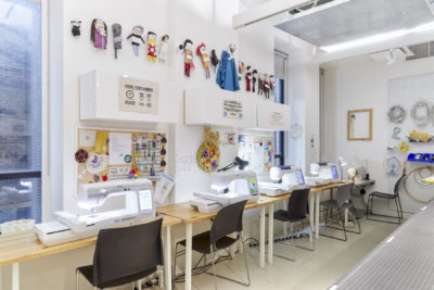 An interior view of the BFA Fine Arts Fibers Lab Facility, showing a row of digital embroidery stations with student artwork hanging above them.