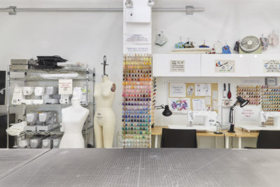 Fibers Lab Facility |SVA BFA Fine Arts. A large cutting table in the foreground with a rack of sewing machines and dress forms behind on the left and two embroidery machines on the right.
