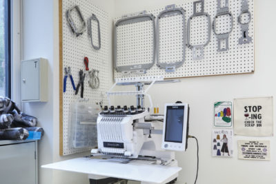 Fibers Lab Facility |SVA BFA Fine Arts. A Brother 10-needle embroidery machine sits below pegboard racks holding hoops and tools.