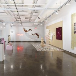"Installation view of the exhibiton titled ""The Politics of Identity"" at the SVA Chelsea Gallery. The view shows works of sculpture, painting, and mixed-media pieces spread throughout the room."