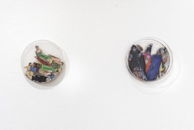 Collages of portraits inside of round petri dishes are mounted on the wall