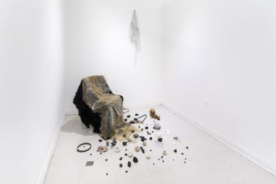 Fabric and skin like material draped over a chair in the corner of a white room, with tiny found objects scattered on the floor