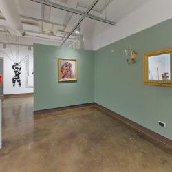 "An installation view of an exhibition at the SVA Chelsea gallery titled ""Sticks and Stones May Break My Bones, But Words Will Never Hurt Me"". The view features a wall on the right hand side painted in a light green golor. On the right side a sculpture sits on a white pedestal. The artwork photographed in the center is by Hayley McCormack."