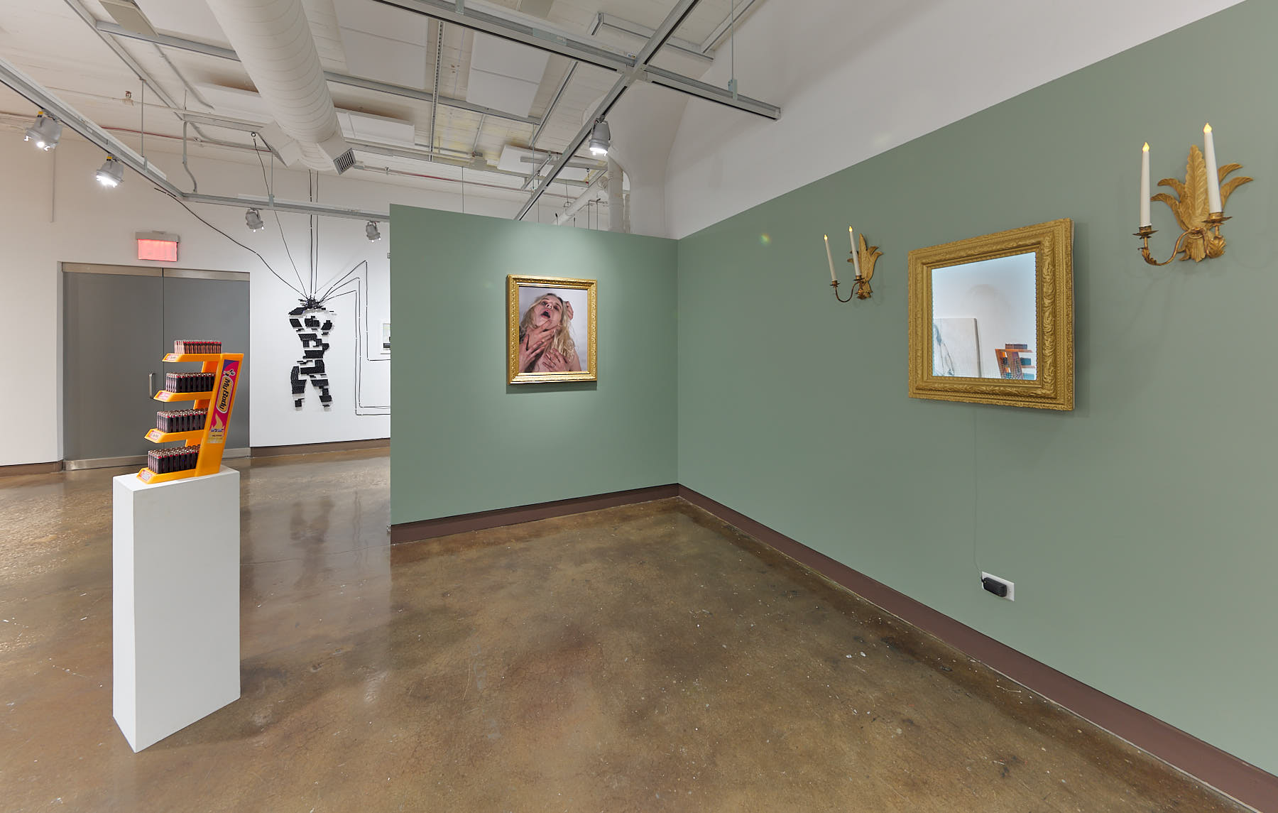 """An installation view of an exhibition at the SVA Chelsea gallery titled """"Sticks and Stones May Break My Bones, But Words Will Never Hurt Me"""". The view features a wall on the right hand side painted in a light green golor. On the right side a sculpture sits on a white pedestal. The artwork photographed in the center is by Hayley McCormack."""