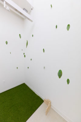 3d printed leaves hang from fishing line in a white room with astroturf carpet.