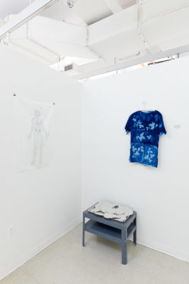 In the corner of a white room sits a small grey table with cement discs, above hangs a dark blue t-shirt with a bleached leaf pattern