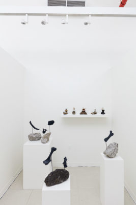 In a white room, a wall mounted shelf and 3 pedestals hold sculptures made of found natural materials