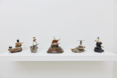 Five sculptures rest on a shelf. Each sculpture is composed of neatly stacked found objects, coated in resin.