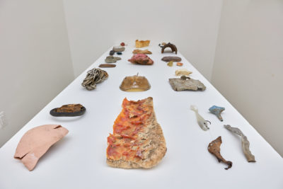 In a white room, a wall mounted shelf and table hold sculptures made of found natural materials