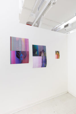 3 abstract photographs of varying sizes hang on a wall, spaced unevenly.