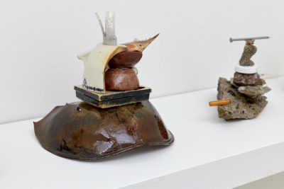 Two sculptures composed of neatly stacked found objects, such as crab shells, cigarette butts, nails and coral