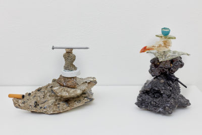 Two sculptures composed of neatly stacked found objects, such as cigarette butts, nails, coral, bottle caps and broken glassware