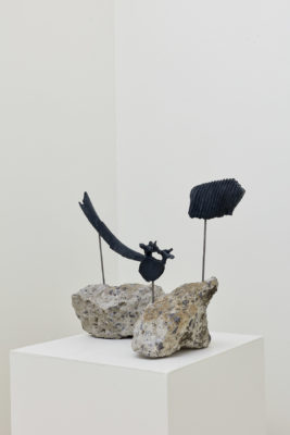 Sculptures made of rock with a bone extruding from them rest on a pedestal