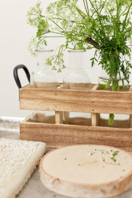 Wooden trays holding glass bottles and fresh cut greenery