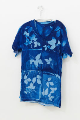 A dark blue t-shirt with a bleached leaf pattern hangs on a white wall