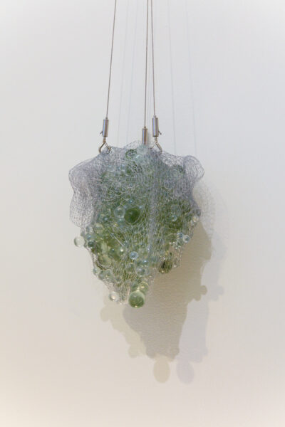 A mass of glass marbles being suspended from a wall, held in a ripped mesh bag.
