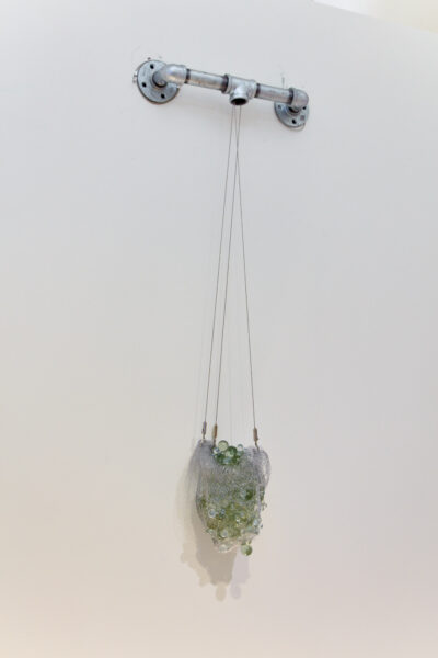 Lidia Tomaj , Faucet, 2021. Metal, pipes, mesh and glass. 8 x 23 inches.