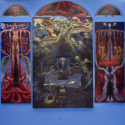Four paintings hang on a blue wall. There is a large central painting with green figures floating around in abstract space. There is a square hole in the center of this painting that houses a smaller portrait. To the left and right of the central painting are two paintings with the same composition and identical figures but in different moments of time. Above the paintings there are three arched openings that have been painted onto the wall. Inside the openings are three separate figures.