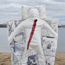 A woman with an abstract bed-like clothes standing in the middle of the photo, on the clothes are doodles of dream scenes and a bruise in the center.