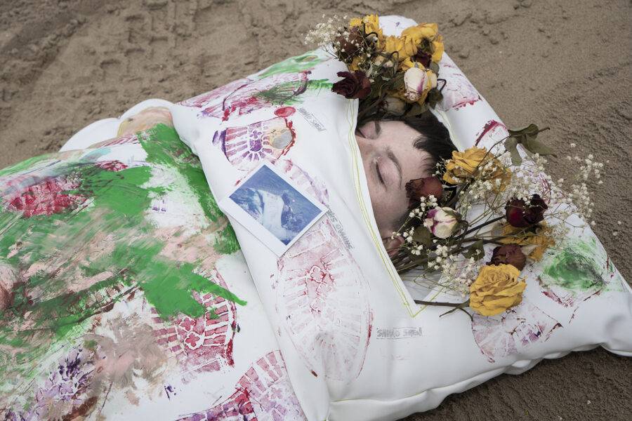 A woman with an abstract bed-like clothes standing in the middle of the photo by the beach, on the bed are paintings of colorful disorganized footprints.