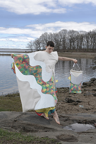 A woman wearing an abstract bed-like clothes with colors floating like a river on it.