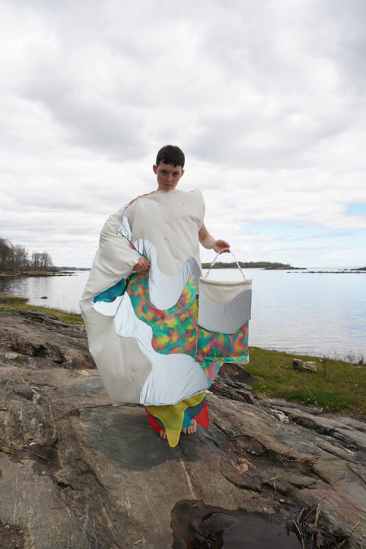 A woman wearing an abstract bed-like clothes with colors floating like a river on it