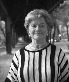 Black and white portrait of Amei Wallach. She is wearing a striped blouse.