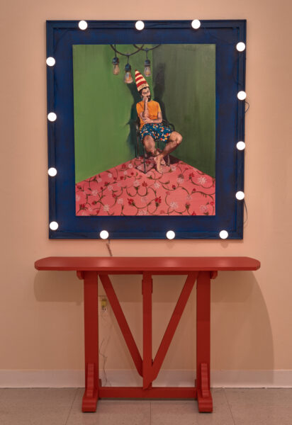A painting depicting a depressed man sitting in a corner of a room with a dunce cap on his head and his mickey mouse shorts. The walls are dull and green with a brightly decorative carpet of pink acting as a contrast to add some color and life to the overall setting. The painting is surrounded by a handmade frame that looks like a vanity mirror with a red painted table in front of it.