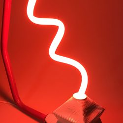 A sculpture by Dakin Platt. The sculpture is has a rod and base holding a thin twisted neon light. The color of the light is bright red. The background is a plain backdrop.