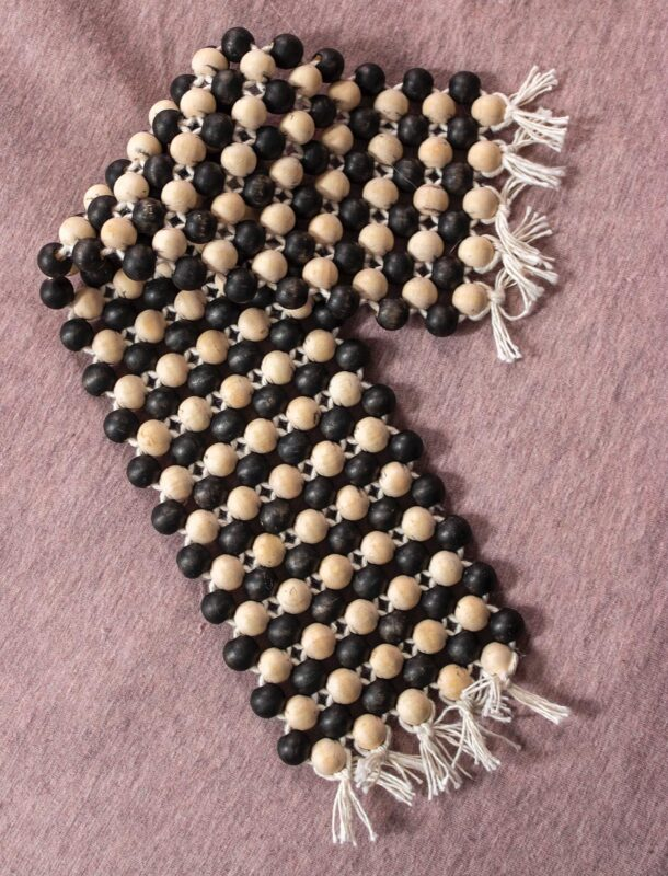 Emma Fasciolo: Beaded Blanket (in progress), 2020. Wood beads and tool.