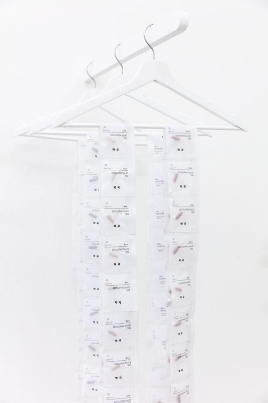 Antonia-Marie Kim, Untitled, 2020. Prescription pills, bottles, fabric, vellum, paper, coat hangers, acrylic plexiglass, and wood. Dimensions variable. Detail.
