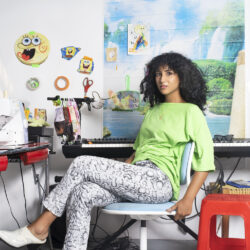 A photograph of Farah Al-Qasimi in her studio. Farah is seated on a chair in the foreground looking at the camera. There is a piano keyboard behind her and other ephemera hanging on the wall behind her.