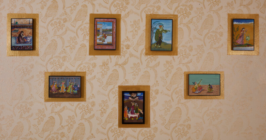 An installation shot of seven framed miniatures out of fourteen hung on a patterned wall with house paint.