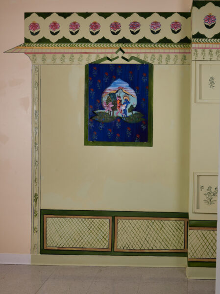Inspired by the early days of the pandemic, this painting shows two demons fighting over a paper towel in a somewhat erotical manner in the middle of a fantastical garden. The wooden frame cut out in a shape of a motif acts as a window to this moment. The painting sits inside a Jharoka, a type of overhanging enclosed balcony used in the architecture of Rajasthan, painted with house paint directly on the wall.