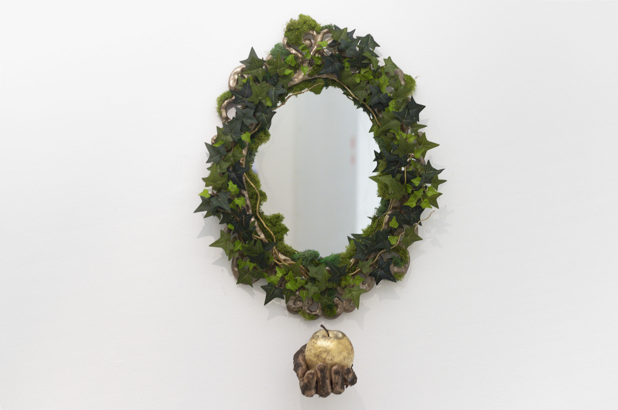 A round ornate gold mirror covered in artificial ivy and moss, below the mirror is a hand facing the viewer holding a golden apple. The hand is covered in dirt.