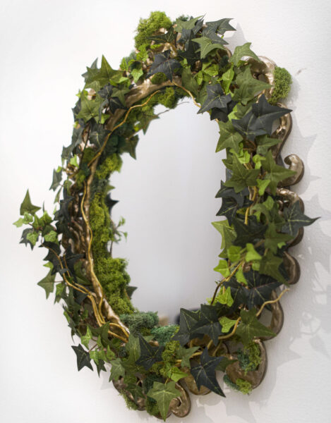 Detail shot. A round ornate gold mirror covered in artificial ivy and moss, below the mirror is a hand facing the viewer holding a golden apple. The hand is covered in dirt.