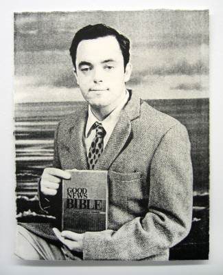 A black and white portrait of a man holding a book titled