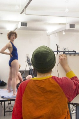 A student in the midst of drawing a still life from a model. In the foreground of the image a student is faced away from the camera and is drawing on their easel. In the background, to the left, are two models on a platform. On model is standing and wearing a blue swimsuit. The other model is sitting and wearing dark shorts.