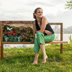 Portrait of Jenifer Wightman sit down on a park bench. Next to the artist there is a painting. The background incudes the skyline of a city.