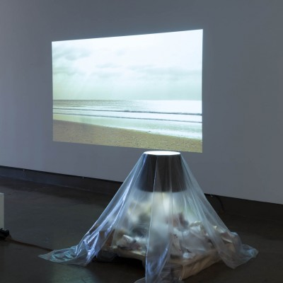 "Jeremiah Lewis: ""Sitting at The Dock"". 2013. Light projector, found objects (house lamp, studio trash, plastic vellum, trunk, 2 pillows). Dimensions variable."