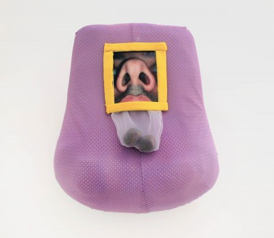 """Jordany Genao: """"Untitled"""". 2013. Foam, athletic fabric dyed lavender, yellow athletic fabric, printed nose image, clear fabric, avocado seeds. 14x13"""""""