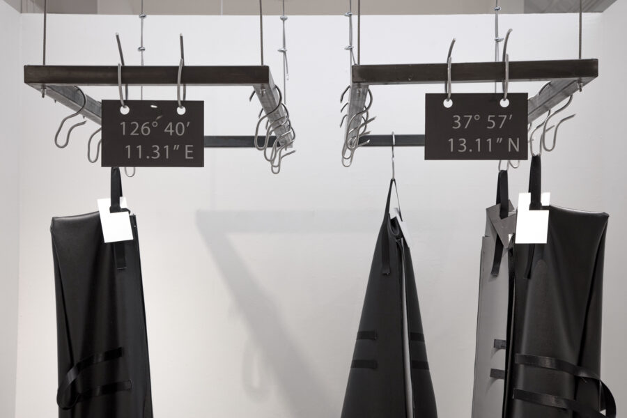 Close-up view of the two metal racks. Each metal rack has a sign 126 degrees, 40 minutes, 11.31 seconds east and 37 degrees, 57 minutes, 13.11 seconds north