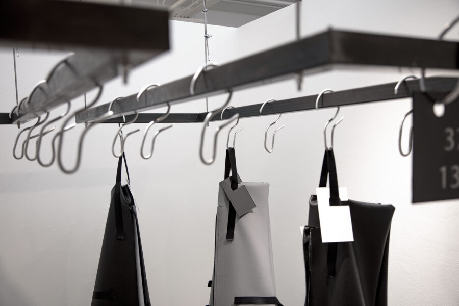 Close-up view of body bags and hooks hanging on the metal racks
