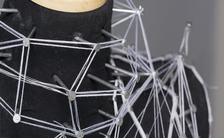 Close-up view of the upper body of a mannequin that have nails hammered across the surface and white threads stretching in between every nail forming a pattern