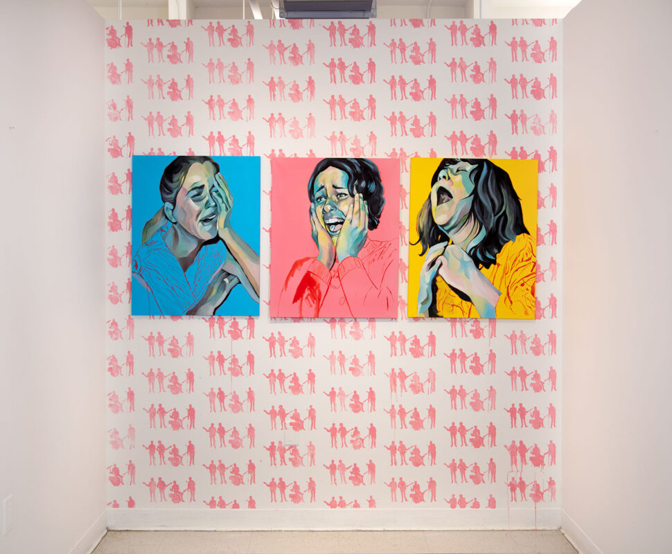 Three paintings of screaming young women are installed on the far wall of a room with 3 walls. There is a pink painting in the center, a yellow painting on the right, and a blue painting on the left. On the back wall behind the paintings there is a repeated stencil painted in pink of silhouettes of the Beatles playing their instruments.