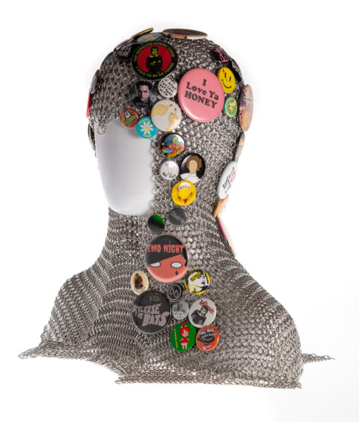 A chainmaille coif displayed on a white plastic mannequin head. The coif is adorned with pinback buttons of various sizes and colors. In this photo the left side of the coif is visible.