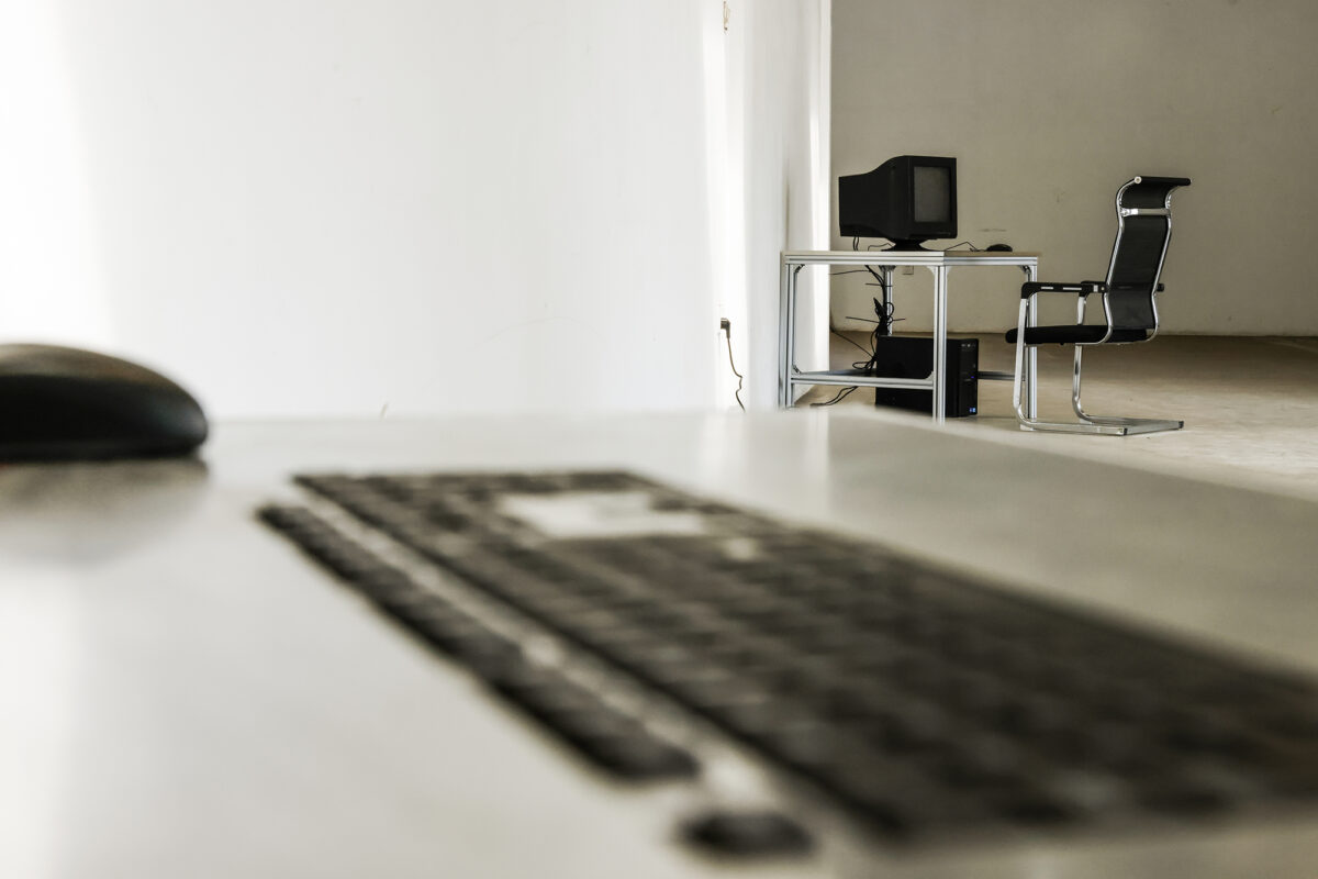 Photograph by Jiaqi Li. The photo shows a blurred computer keyboard in the foreground with a computer and desk in the background.