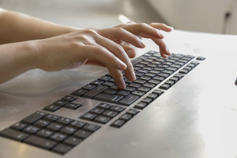 Hands positioned over a computer keyboard in the act of typing. Video still.