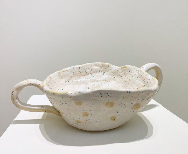 Ivory and beige color pottery with decorative blue and orange small dots, and two handles on each side of the pottery.